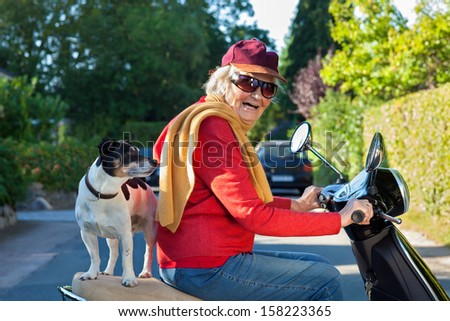 Laughing senior woman riding a scooter with her dog. Elderly lady laughing happily as she takes her dog, a small jack russell terrier, for a scooter ride balanced on the pillion behind her