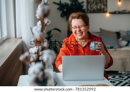 laughing Senior woman using laptop for websurfing. Mature lady with cup of coffee watching funny movie. #781352992