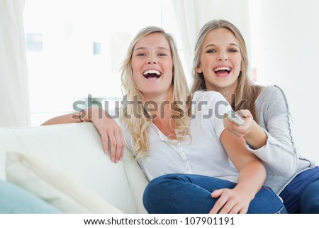 Laughing sisters on the couch as they watch tv and look at the camera