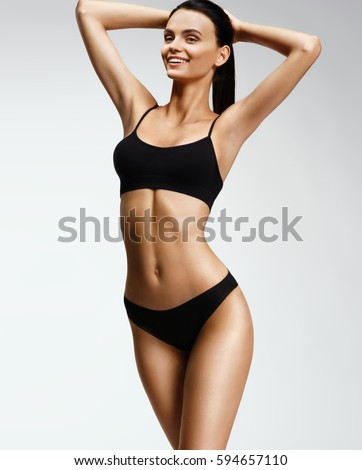 Stock Photo Laughing sporty girl in black bikini posing on grey background. Photo of attractive girl with slim toned body. Beauty and body care concept