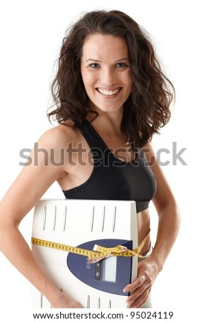 Laughing sporty woman holding scale with tape measure, looking successful and happy.?