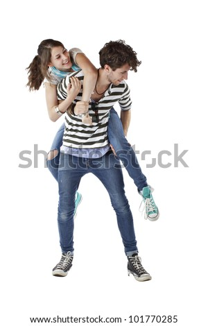 Laughing teen girl playfully jumps up on teen boy's back. Both wear stripes, jeans, and sneakers. Vertical, isolated on white, copy space.