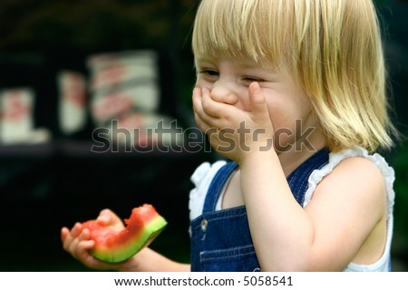 Laughing toddler girl with one hand covering mouth while another holding a piece of juicy red watermelon, having fun in the garden.