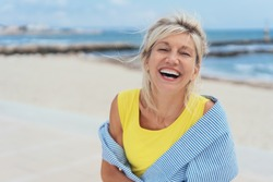 Laughing vivacious blond woman with a sense of humour standing on a tropical beach with copy space