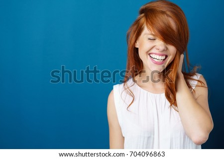 Laughing vivacious young redhead woman with a beaming smile holding her long red hair over one hand on blue with copy space