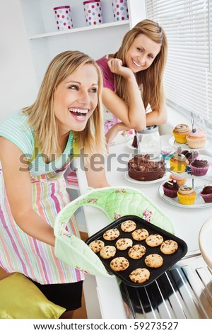 Laughing woman baking together in the kitchen