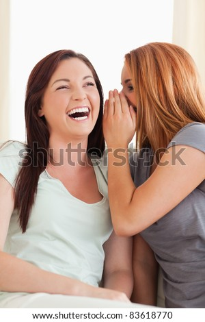 Laughing woman being told something living room