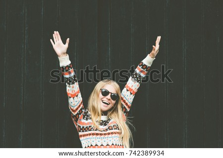 Laughing Woman happy hands up raised wellness Lifestyle fashion emotional girl wearing cozy sweater against wooden black background