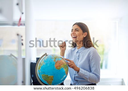 Laughing woman pointing to country on globe in bright classroom or office for concept about education and geography