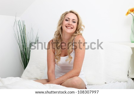 Laughing woman relaxing on her bed Laughing woman with a lovely smile relaxing on her bed in her lingerie as she enjoys a leisurely morning