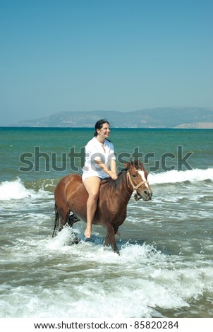 Laughing woman riding horse in water sea with waves