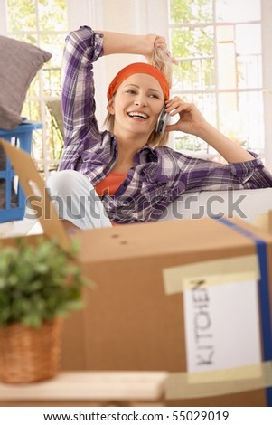Laughing woman taking break at moving house, talking on mobilephone.