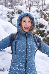 Laughing woman throws snow in the park, winter fun, winter time.
