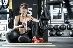 Laughing woman with curly hair sits on the floor in the gym on the background of the partition. She wears dark sportswear with red sneakers. Girl leans on the black ball and holds a bottle of water.
