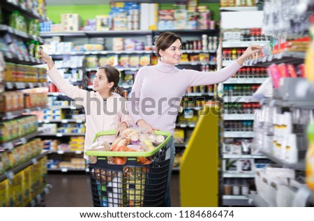 Laughing woman with daughter shopping with shopping cart in supermarket