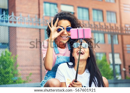 Laughing woman with friend making OK symbol with thumb and fingers while seated in front of camera on selfie stick