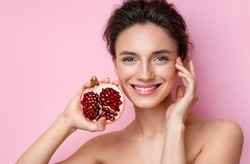Laughing woman with half an pomegranate. Photo of beautiful  woman with perfect makeup on pink background. Beauty & Skin care concept