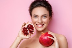 Laughing woman with pomegranates. Photo of attractive woman with perfect makeup on pink background. Beauty & Skin care concept