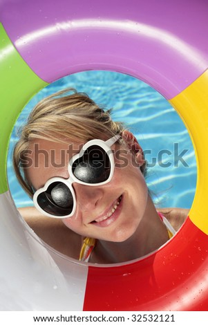 Laughing woman with sunglasses and inflatable toy