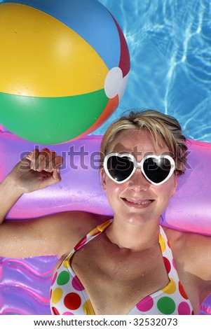 Laughing woman with sunglasses and inflatable toys