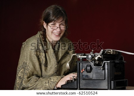 laughing woman wrapped in a green shawl typing on an antique typewriter against a dark red background