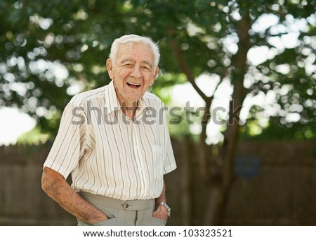 Laughing 90 year old senior man standing outside