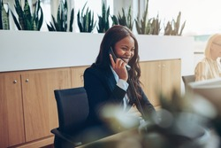 Laughing young African American businesswoman talking on a telephone while working at an office reception desk with a colleague