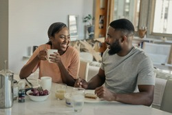 Laughing young African American couple sitting together at their kitchen table in the morning talking and eating breakfast