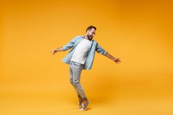 Laughing young bearded man in casual blue shirt posing isolated on yellow orange background studio portrait. People emotions lifestyle concept. Mock up copy space. Standing on toes, spreading hands