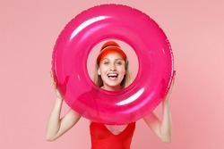 Laughing young blonde woman girl in red one-piece swimsuit cap posing isolated on pink wall background. People summer vacation rest lifestyle concept. Mock up copy space. Hold swim inflatable ring