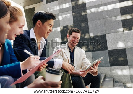 Laughing young business people sitting on steps and watching funny video on tablet computer in hands of colleague stock photo