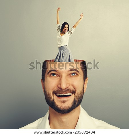 laughing young businessman with open head. young excited businesswoman dancing and raising hands up in the man\'s head. photo over grey background