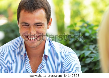 Laughing young handsome man sitting in front of his girlfriend