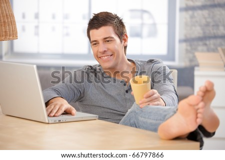 Laughing young man enjoying using laptop computer at home, holding tea cup, looking at screen with bare feet on table.?