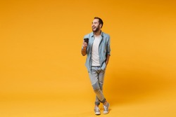 Laughing young man in casual blue shirt posing isolated on yellow orange background, studio portrait. People emotions lifestyle concept. Mock up copy space. Hold cup of coffee or tea, looking aside