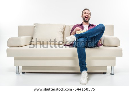 Laughing young man sitting on couch with popcorn isolated on white #544158595