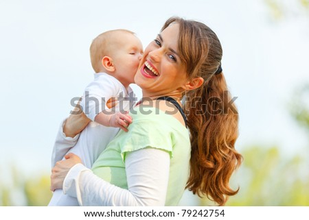 Laughing young mother hugging her baby in hands outdoors