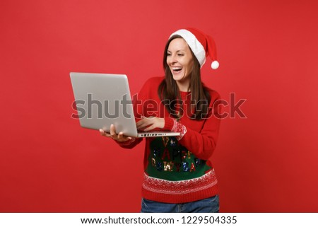 Laughing young Santa girl in knitted sweater, Christmas hat working, typing on laptop pc computer isolated on red background. Happy New Year 2019 celebration holiday party concept. Mock up copy space