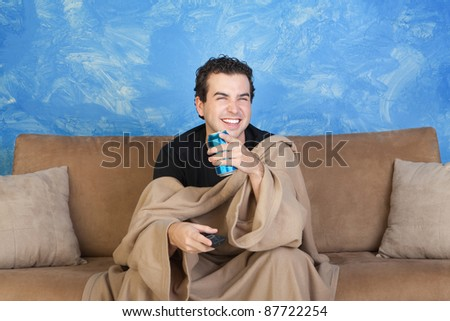 Laughing young with blanket on sofa with beverage can and remote control