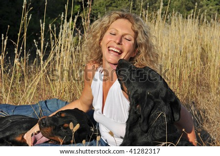 laughing young woman and her two dogs: rottweiler and french shepherd