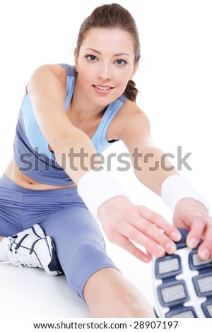 laughing young woman doing physical stretching on the floor - stock photo