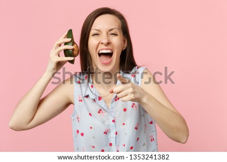 Laughing young woman pointing index finger on camera, holding half of fresh ripe avocado fruit isolated on pink pastel background. People vivid lifestyle relax vacation concept. Mock up copy space #1353241382