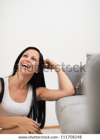 Laughing young woman sitting on floor  near couch