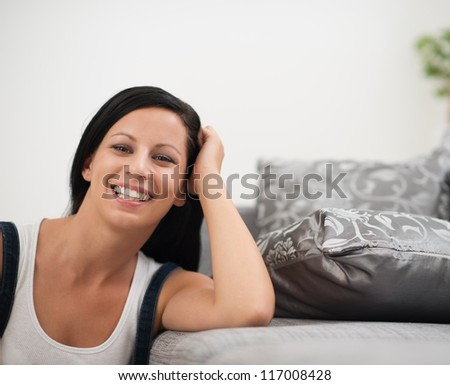 Laughing young woman sitting on floor near sofa