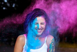 Laughing young woman with dry color powder Holi exploding around her