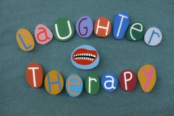Laughter therapy, a type of complementary therapy also called humor therapy composed with multi colored stone letters and mounth design over green sand