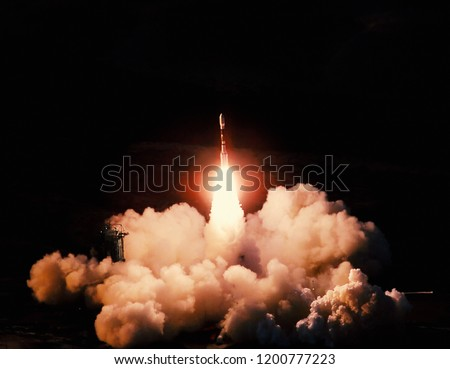 Launch of the spaceship from the spaceport at night. Flight of space shuttle in clouds of smoke. Some elements of this image are furnished by NASA