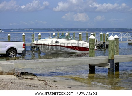 Launching a trailer boat on the boat ramp next to a wooden pier in the Tampa Bay, Florida USA