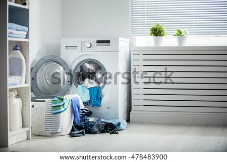 laundry. A washing machine and a pile of dirty clothes at home