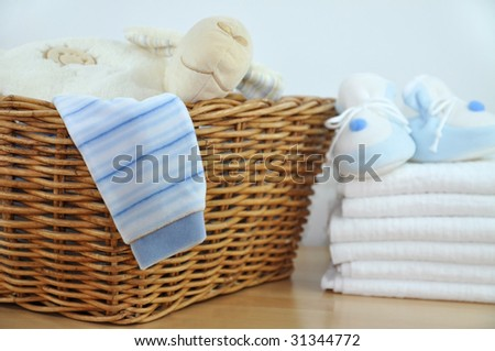 Laundry basket with blue clothes and slippers on a pile of diapers